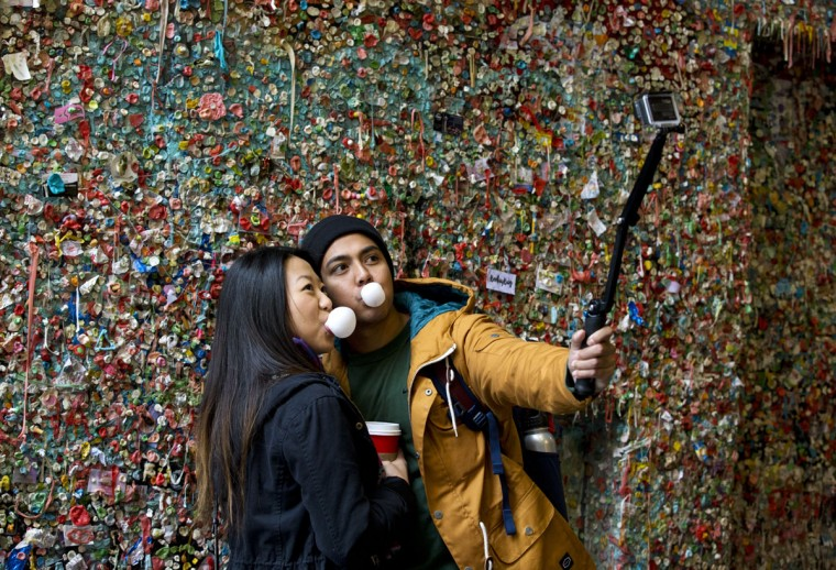 Jessica Wang, left, and Michael Teylan, both of Los Angeles, take a photo at Seattle's famous gum wall at Pike Place Market, Monday, Nov. 9, 2015. (AP Photo/Ted S. Warren)