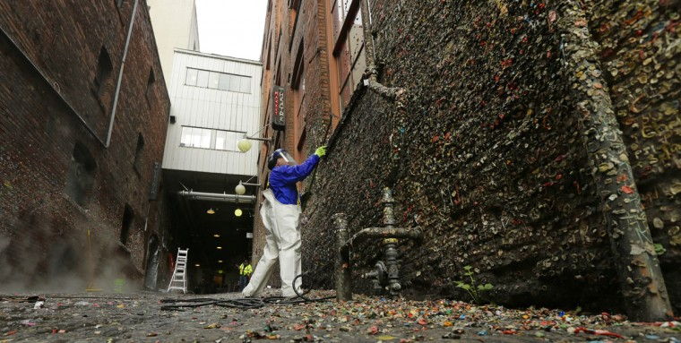"""Fernando Soberania works to clean layers of gum from Seattle's famous """"gum wall"""" at Pike Place Market, Tuesday, Nov. 10, 2015. (AP Photo/Ted S. Warren)"""