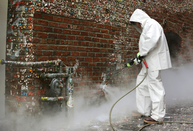 """Javier Ramirez uses a high-temperature pressure washer to clean layers of gum from Seattle's famous """"gum wall"""" at Pike Place Market, Tuesday, Nov. 10, 2015. (AP Photo/Ted S. Warren)"""
