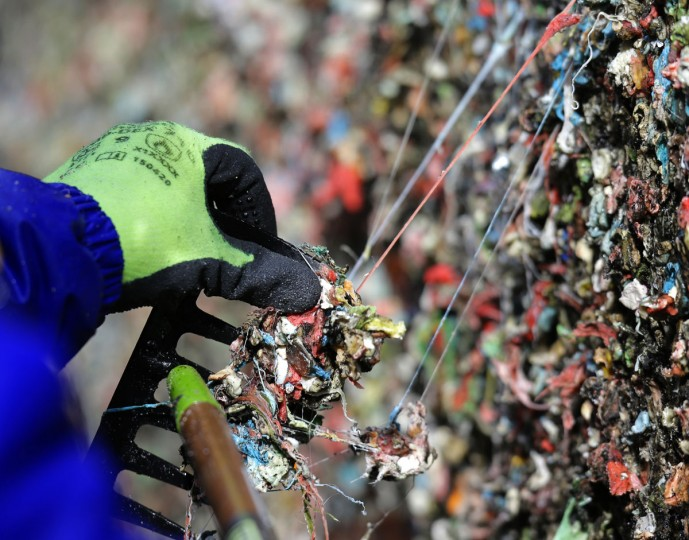 """Fernando Soberania uses a tool to scrape layers of gum from Seattle's famous """"gum wall"""" at Pike Place Market, Tuesday, Nov. 10, 2015. (AP Photo/Ted S. Warren)"""