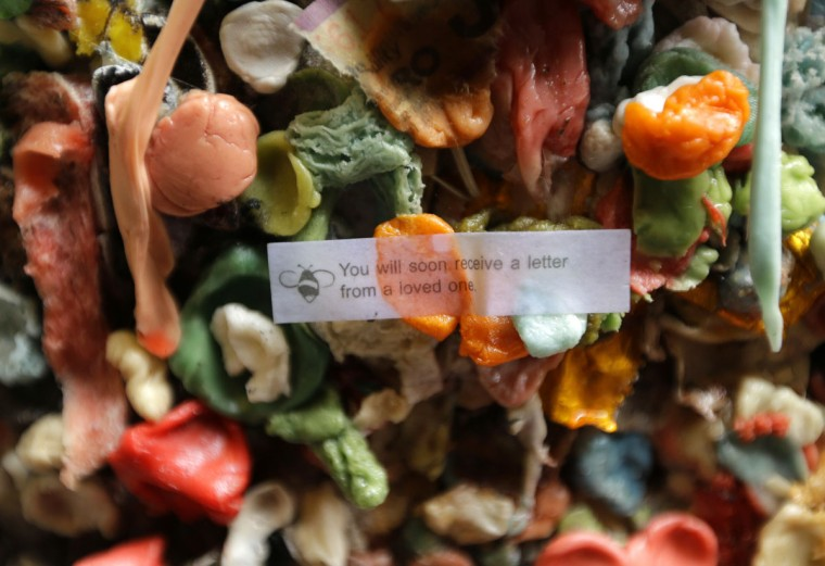 A fortune from a fortune cookie is stuck to layers of gum on a wall at Seattle's famous gum wall at Pike Place Market, Monday, Nov. 9, 2015. (AP Photo/Ted S. Warren)