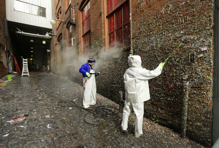 """Fernando Soberania, left, and Javier Ramirez, right, work to clean layers of gum from Seattle's famous """"gum wall"""" at Pike Place Market, Tuesday, Nov. 10, 2015. (AP Photo/Ted S. Warren)"""