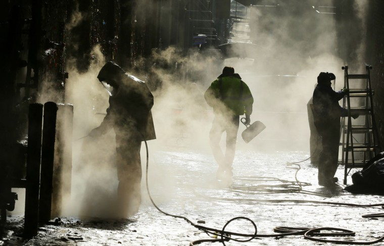 """Workers use a high-temperature pressure washer to clean layers of gum from Seattle's famous """"gum wall"""" at Pike Place Market, Tuesday, Nov. 10, 2015. (AP Photo/Ted S. Warren)"""