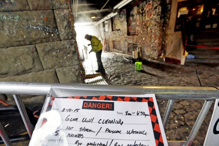 """A worker sweeps up piles of old gum being cleaned off the walls around him by powerful steam cleaners at a """"gum wall,"""" several walls actually, Tuesday, Nov. 10, 2015, in Seattle. (AP Photo/Elaine Thompson)"""