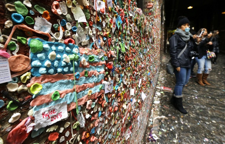 """The likeness of an American flag made from pieces of gum sticks to a wall at Seattle's """"gum wall"""" at Pike Place Market, Monday, Nov. 9, 2015. (AP Photo/Ted S. Warren)"""