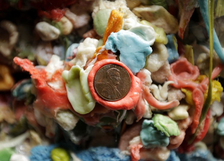 """A penny is stuck to layers of gum on a wall at Seattle's """"gum wall"""" at Pike Place Market, Monday, Nov. 9, 2015. (AP Photo/Ted S. Warren)"""