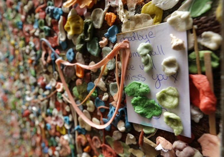 """A note that reads """"Goodbye gum wall, we will miss you,"""" sticks to a wall partially obscured by gum, Monday, Nov. 9, 2015, at Seattle's """"gum wall"""" at Pike Place Market. (AP Photo/Ted S. Warren)"""