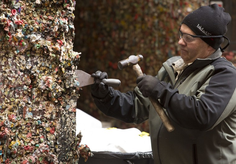 A worker chisels off top layers of the 20-years worth of chewing gum that has accumulated in Post Alley at the Pike Place Market in Seattle, Washington on November 11, 2015. (JASON REDMOND/AFP/Getty Images)