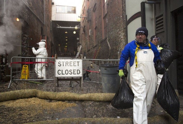 Workers carry trash bags filled with chewing gum that is being removed from the walls in Post Alley at Pike Place Market in Seattle, Washington on November 11, 2015. (JASON REDMOND/AFP/Getty Images)