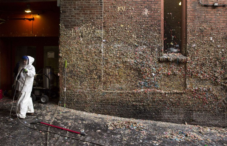 A worker is pictured holding a pressure washer as 20-years worth of chewing gum is removed from Post Alley at Pike Place Market in Seattle, Washington on November 11, 2015. (JASON REDMOND/AFP/Getty Images)