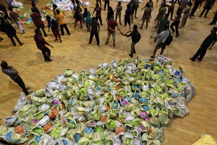 Volunteers sort relief material to be distributed to flood victims at the Jawarhalal Nehru Indoor stadium in Chennai, India, Sunday, Dec. 6, 2015. Indian authorities were investigating possible negligence after 18 hospital patients died when rainwaters from massive floods in southern Tamil Nadu state knocked out generators and switched off ventilators.The worst flooding in a century in Tamil Nadu has left scores of people dead since November. (AP Photo/Arun Sankar K)