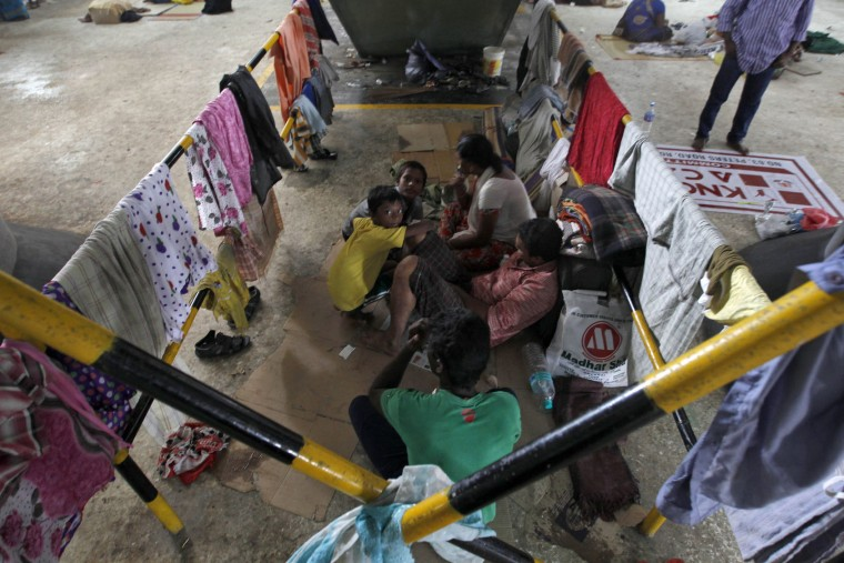 A family of flood victims huddle together at a temporary shelter at a railway station in Chennai, India, Sunday, Dec. 6, 2015. Indian authorities were investigating possible negligence after 18 hospital patients died when rainwaters from massive floods in southern Tamil Nadu state knocked out generators and switched off ventilators.The worst flooding in a century in Tamil Nadu has left scores of people dead since November. (AP Photo/Arun Sankar K)