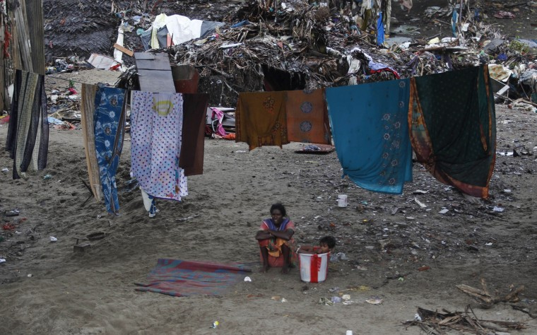 A resident sits near washed clothes left to dry after they were recovered from their flood damaged houses on the banks of the Adyar River in Chennai, India, Sunday, Dec. 6, 2015. Indian authorities were investigating possible negligence after 18 hospital patients died when rainwaters from massive floods in southern Tamil Nadu state knocked out generators and switched off ventilators.The worst flooding in a century in Tamil Nadu has left scores of people dead since November. (AP Photo/Arun Sankar K)