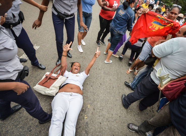 A member of the Ladies in White Human Rights organization lies on the ground as policewomen approach to arrest her on December 10, 2015 in Havana during a demo for the Human Rights Day. (Adalberto Roque/AFP/Getty Images)