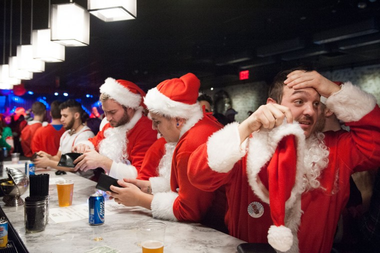Men dressed as a Santa drink at a bar called The Hall during the annual SantaCon pub crawl December 12, 2015 in the Brooklyn borough of New York City. Hundreds of revelers take part in the holiday pub crawl, though some local bars and businesses have banned participants in an effort to avoid the typically rowdy SantaCon crowds. (Stephanie Keith/Getty Images)