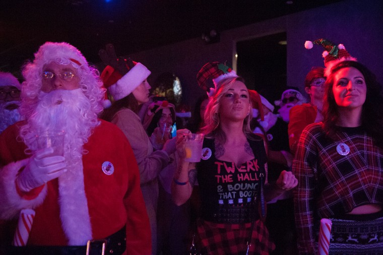 A man dressed as a Santa listens to a live band with two women at a bar called The Hall during the annual SantaCon pub crawl December 12, 2015 in the Brooklyn borough of New York City. Hundreds of revelers take part in the holiday pub crawl, though some local bars and businesses have banned participants in an effort to avoid the typically rowdy SantaCon crowds. (Stephanie Keith/Getty Images)