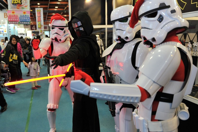 "Local fans dressed as Star Wars character Kylo Ren (2nd L) and Stormtroopers pose during a toy exhibition in Taipei on December 17, 2015. Ever since 1977, when ""Star Wars"" introduced the world to The Force, Jedi knights, Darth Vader, Wookiees and clever droids R2-D2 and C3PO, the sci-fi saga has built a devoted global fan base that spans the generations. (Sam Yeh/AFP/Getty Images)"