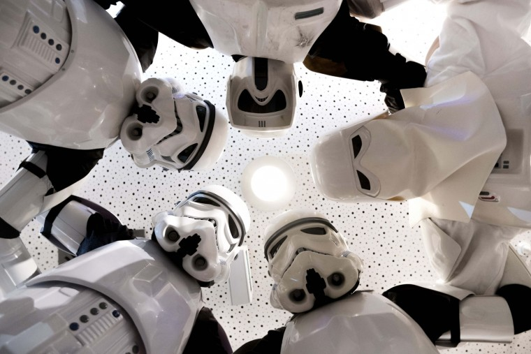 "Members of the Star Wars ""Star Wars Fans Nuernberg"" fan club dressed as ""Stormtrooper"" characters pose for a photo at a cinema in Nuremberg, southern Germany, on December 16, 2015. Ever since 1977, when ""Star Wars"" introduced the world to The Force, Jedi knights, Darth Vader, Wookiees and clever droids R2-D2 and C3PO, the sci-fi saga has built a devoted global fan base that spans the generations. ""Star Wars: The Force Awakens"" had its German Premiere on December 16, 2015. (DPA/Nicolas Armer Germany/AFP/Getty Images)"