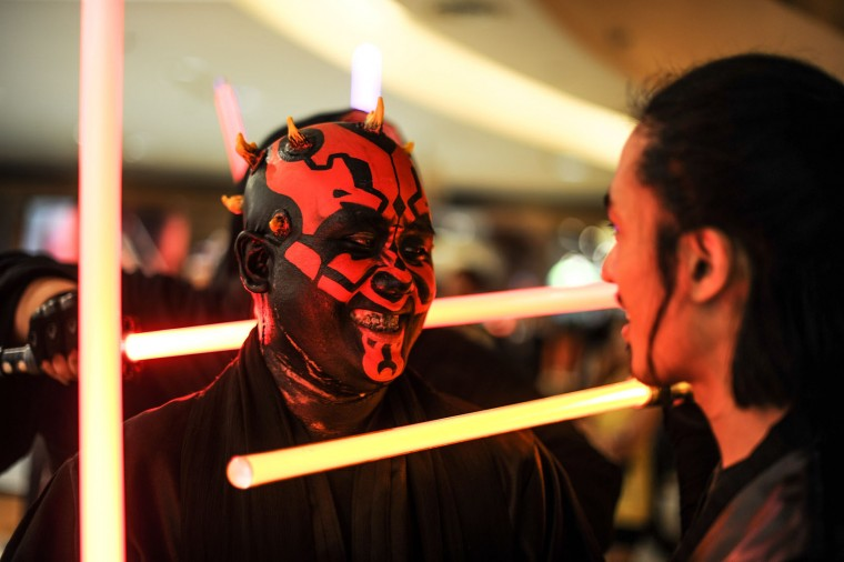 A member of Malaysia's Star Wars Fan Club dressed as Darth Maul (C) attends a viewing of 'Star Wars: The Force Awakens' at a cinema in Subang, outside Kuala Lumpur on December 17, 2015. (Mohd Rasfan/AFP/Getty Images)