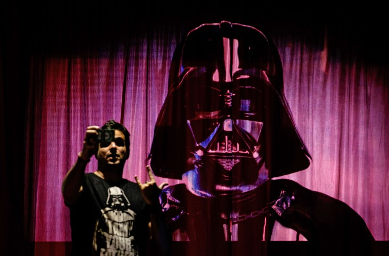"A fan takes a selfie with projected images of the film ""Star Wars"", during the opening of the Rio Mapping Festival 2015, on December 17, 2015, in Rio de Janeiro, Brazil. (Yasuyoshi Chiba/AFP/Getty Images)"