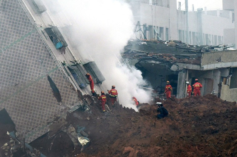 Rescuers search for survivors on a damaged building following a landslide in Shenzhen, in south China's Guangdong province, Sunday, Dec. 20, 2015. (Chinatopix via AP)