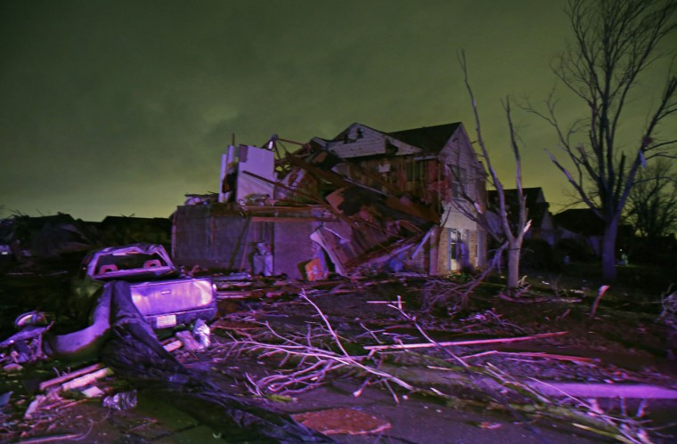 Debris lies on the ground near a home that was heavily damaged by a tornado in Rowlett, Texas, Saturday, Dec. 26, 2015. Tornadoes swept through the Dallas area after dark on Saturday evening causing significant damage. (Guy Reynolds/The Dallas Morning News via AP)