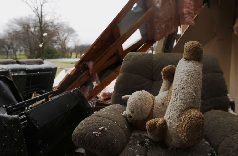 A stuffed animal sits on a comfort chair inside a house destroyed by Saturday night's tornado in Copeville, Texas, Sunday, Dec. 27, 2015. Tornadoes that swept through the Dallas area caused substantial damage and at least 11 people died either from the storm or related traffic accidents and dozens of people were injured. (Rachel Woolf/The Dallas Morning News via AP)