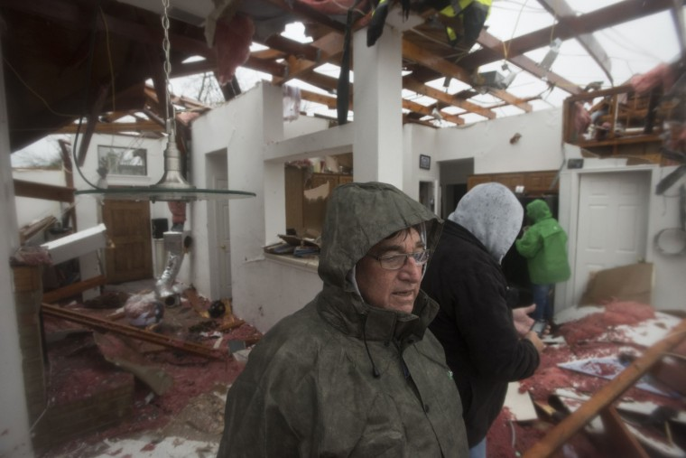 Bob Moore stands in his home in Rowlett, Texas, Sunday, Dec. 27, 2015, the morning after it was struck by a tornado. At least 11 people died and dozens were injured in apparently strong tornadoes that swept through the Dallas area and caused substantial damage this weekend. (AP Photo/Rex C. Curry)