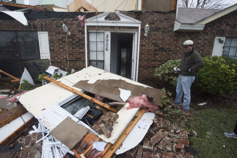 Michael Downard stands outside his house in Rowlett, Texas, Sunday, Dec. 27, 2015, the morning after it was struck by a tornado. At least 11 people died and dozens were injured in apparently strong tornadoes that swept through the Dallas area and caused substantial damage this weekend. (AP Photo/Rex C. Curry)