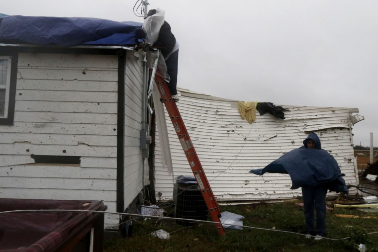 Oscar Garcia, left, and Alicia Aldridge work on fixing Rocky Haddick's, not pictured, roof, off of TX-78 in Copeville, Texas, on Sunday, Dec. 27, 2015, after heavy rain, high winds and tornadoes swept through North Texas the previous night. (Rachel Woolf/Dallas Morning News/TNS)