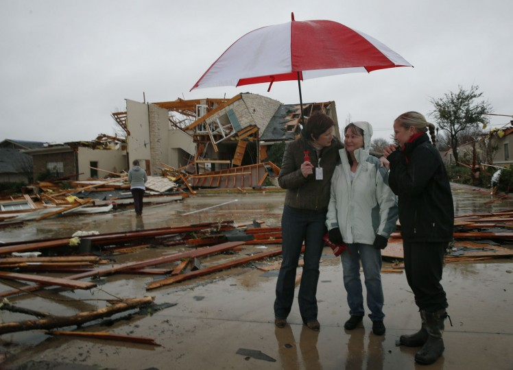 Rendi Black, left, hugs Sandra Trollington, center, with Nicole Perdue on Sunday, Dec. 27, 2015, after a tornado hit Saturday night at the intersection of Dalrock and State Highway 66 in Rowlett, Texas. Trollington is the owner of the State Farm building behind her, and the other two are insurance agents. (Nathan Hunsinger/Dallas Morning News/TNS)