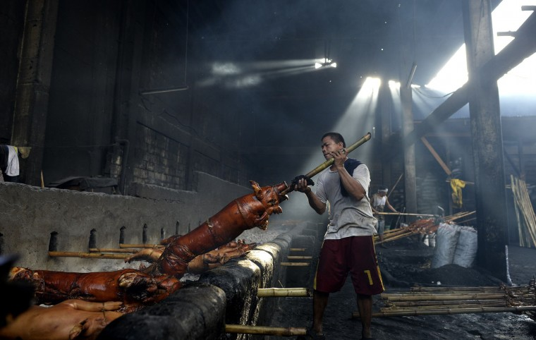 """A worker lifts a roasted bamboo skewered pig off hot coals in Manila on December 23, 2015. """"Lechon"""", or roasted pig, has always been regular fare at Philippine festivities, especially during Christmas and New Year celebrations. The Philippine Christmas season runs from December until the second week of January. (Noel Celis/AFP/Getty Images)"""