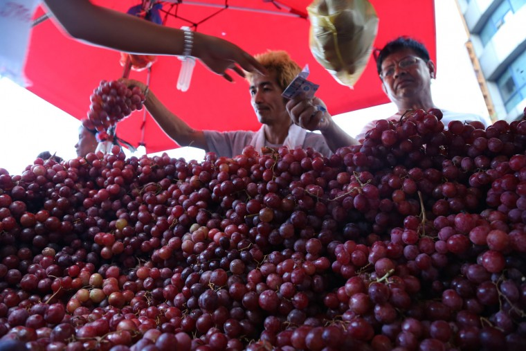 A Filipino man buys grapes at a makeshift stall in downtown Manila, Philippines on Monday, Dec. 28, 2015. Many Filipinos believe that having 12 round fruits of different kinds on the family table will bring good luck during the New Year. (AP Photo/Aaron Favila)