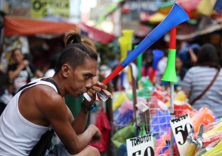 A Filipino man sells plastic horns along makeshift stalls in downtown Manila, Philippines on Monday, Dec. 28, 2015. Many Filipinos believe that noisemakers will drive away evil spirits and bring good luck during the New Year. (AP Photo/Aaron Favila)