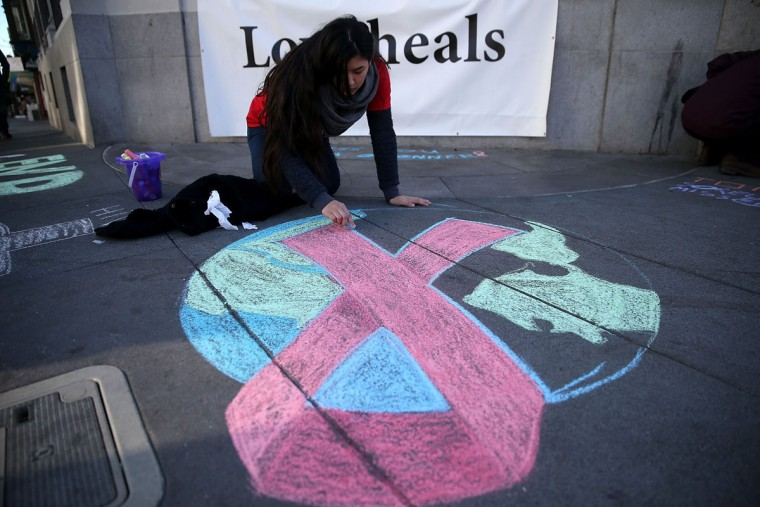 Angelica Tome does a chalk drawing of a red AIDS ribbon on Castro Street on December 1, 2015 in San Francisco, California. To commemorate World AIDS day, dozens of people used chalk to write the names of people who have died from AIDS along San Francisco's Castro Street. World AIDS Day has been observed on December 1, since 1988, and is dedicated to raising awareness of the AIDS pandemic caused by the spread of HIV infection, and to mourn those who have died from the disease. (Photo by Justin Sullivan/Getty Images)