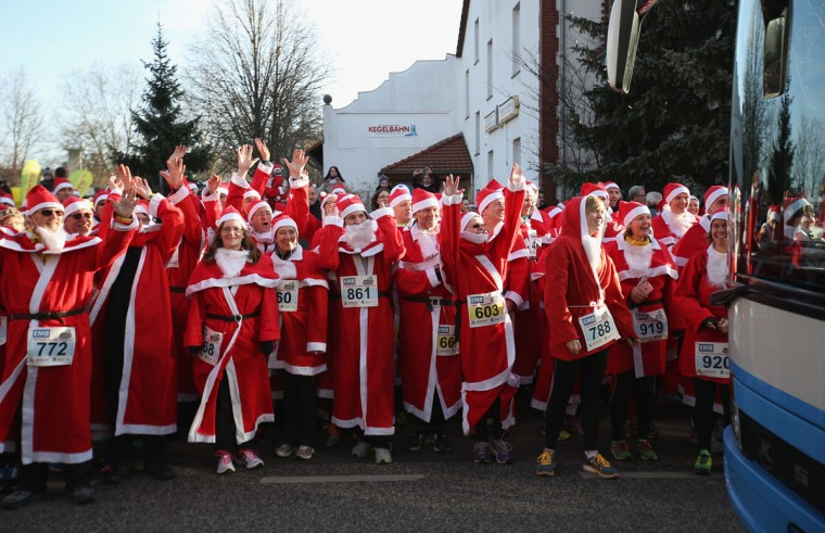 Participants dressed as Santa Claus wave their arms in a wave pattern to a passing bus as they wait to start in the 7th annual Michendorf Santa Run on December 6, 2015 in Michendorf, Germany. A record 900 runners took part in this year's event, which included 2,5km, 5km and 10km races. (Photo by Sean Gallup/Getty Images)