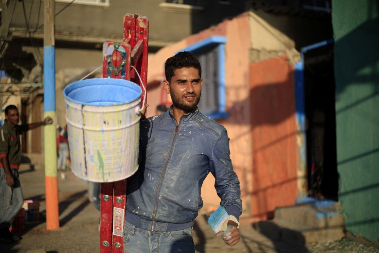 A Palestinian artist paints houses in the al-Shati refugee camp in Gaza City, on November 12, 2015, as he takes part in a project with more than 30 artists funded by Padico holding, a limited public shareholding company traded on the Palestine Exchange (PEX). (AFP Photo/Mohammed Abed)
