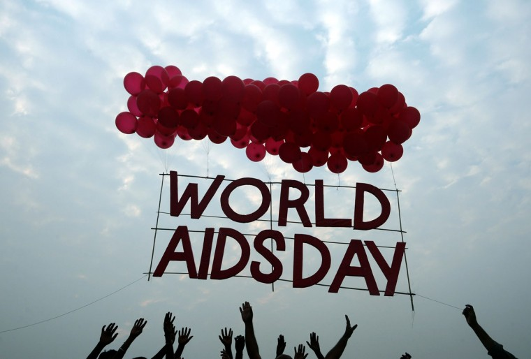 Indian social activists and children release a World AIDS Day awareness sign tied with ballons in Kolkata on December 1, 2015. According to the UN AIDS programme, India had the third-largest number of people living with HIV in the world at the end of 2013 and it accounts for more than half of all AIDS-related deaths in the Asia-Pacific region. In 2012, 140,000 people died in India because of AIDS. The Indian government has been providing free antiretroviral drugs for HIV treatment since 2004, but only 50 percent of those eligible for the treatment were getting it in 2012, according to a report by the World Health Organisation. (AFP Photo/Dibyangshu Sarkar)