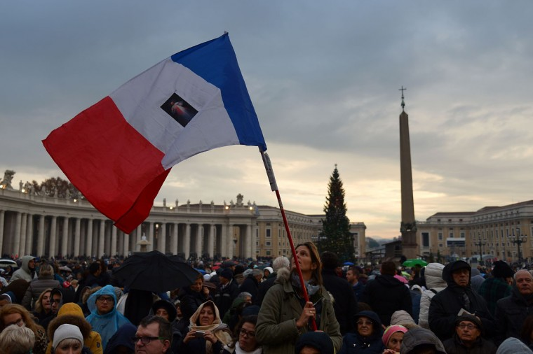 "A pilgrim waves a French national flag on St Peter's square before the start of the Jubilee Year of Mercy, on December 8, 2015 in Vatican. Pope Francis marks the start of an extraordinary Jubilee year for the world's 1.2 billion Catholics by opening a ""Holy Door"" in the walls of St Peter's basilica. At 9.30 am (0830 GMT), the Argentinian pontiff will pronounce the words ""Aperite mihi Porta Iustitiae"" -- Latin for ""open to me the gates of justice"" -- and the door, which is normally bricked up, will be opened. (AFP Photo/Vincenzo Pinto)"