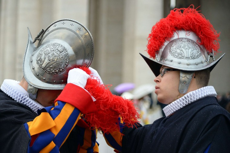 "A Swiss guard helps a colleague to adjust his helmet at St Peter's square before the start of the Jubilee Year of Mercy, on December 8, 2015 in Vatican. Pope Francis marks the start of an extraordinary Jubilee year for the world's 1.2 billion Catholics by opening a ""Holy Door"" in the walls of St Peter's basilica. At 9.30 am (0830 GMT), the Argentinian pontiff will pronounce the words ""Aperite mihi Porta Iustitiae"" -- Latin for ""open to me the gates of justice"" -- and the door, which is normally bricked up, will be opened. (AFP Photo/Vincenzo Pinto)"