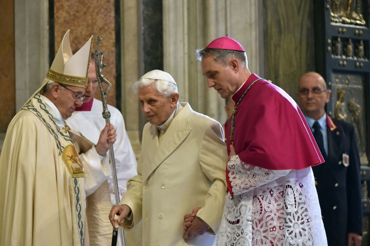 "Pope Emeritus Benedict XVI (C) is helped by the prefect of the papal household Georg Gaenswein (R) as he walks past Pope Francis in St Peter's basilica after the opening of the ""Holy Door"" to mark the start of the Jubilee Year of Mercy, on December 8, 2015 in Vatican. Pope Francis marks the start of an extraordinary Jubilee year for the world's 1.2 billion Catholics by opening a ""Holy Door"" in the walls of St Peter's basilica. At 9.30 am (0830 GMT), the Argentinian pontiff will pronounce the words ""Aperite mihi Porta Iustitiae"" -- Latin for ""open to me the gates of justice"" -- and the door, which is normally bricked up, will be opened. (AFP Photo/Alberto Pizzoli)"