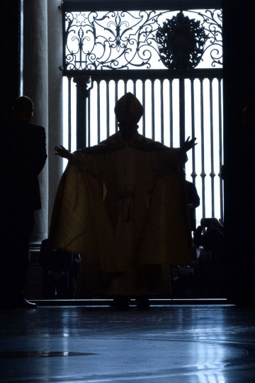 "Pope Francis opens a ""Holy Door"" at St Peter's basilica to mark the start of the Jubilee Year of Mercy, on December 8, 2015 in Vatican. In Catholic tradition, the opening of ""Holy Doors"" in Rome symbolises an invitation from the Church to believers to enter into a renewed relationship with God. (AFP Photo/Alberto Pizzoli)"