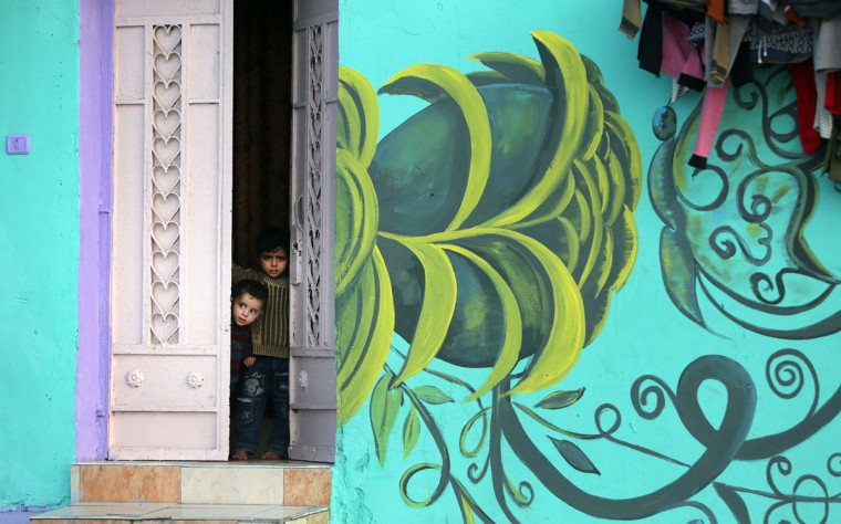 Palestinian children look out of a house painted by Palestinian artists in the al-Shati refugee camp in Gaza City, on December 19, 2015. (AFP Photo/Mahmud Hams)