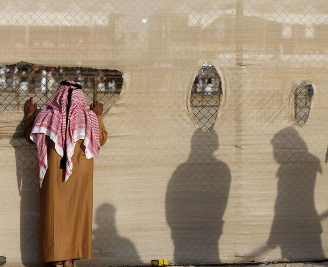 Emirati men peak from behind a chain-link fence during the Mazayin Dhafra Camel Festival in the desert near the city of Madinat Zayed, 150 kms west of Abu Dhabi, on December 26, 2015. (KARIM SAHIB/AFP/Getty Images)