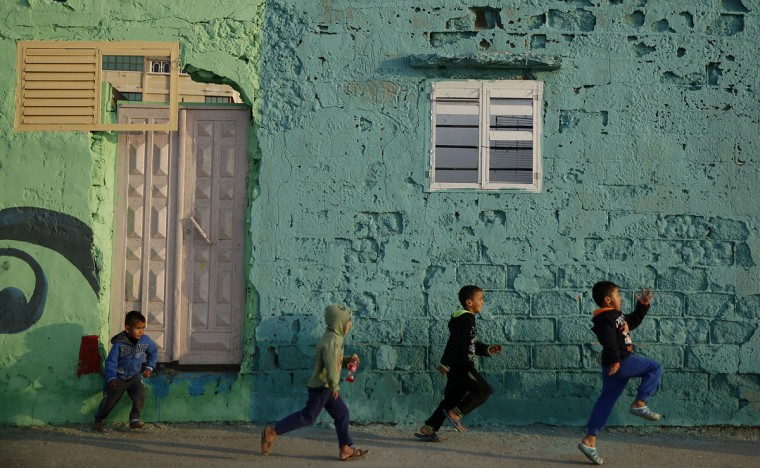 In this Saturday Dec. 19, 2015 photo, Palestinian boys run by a painted house in the Shati Refugee Camp in Gaza City. Shati has always been a symbol of poverty, a grey concrete jungle with 87,000 people packed into one fifth of a square mile (half a square kilometer). But now, overlooking the sewage-contaminated Mediterranean beachfront, the campís houses are covered in vibrant colors. (AP Photo/Hatem Moussa)