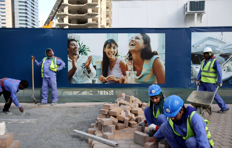 Laborers install paving stones in front of an advertisement for luxury real estate, in the Marina district of Dubai, United Arab Emirates. Armies of low-paid migrant workers, many of them from the Indian Subcontinent, leave behind families and travel to Dubai to build soaring towers like those in the Marina. While the wages they come for offer hope of a better life, they are far too meager for most to ever dream of calling the Marina they built home. (AP Photo/Kamran Jebreili)