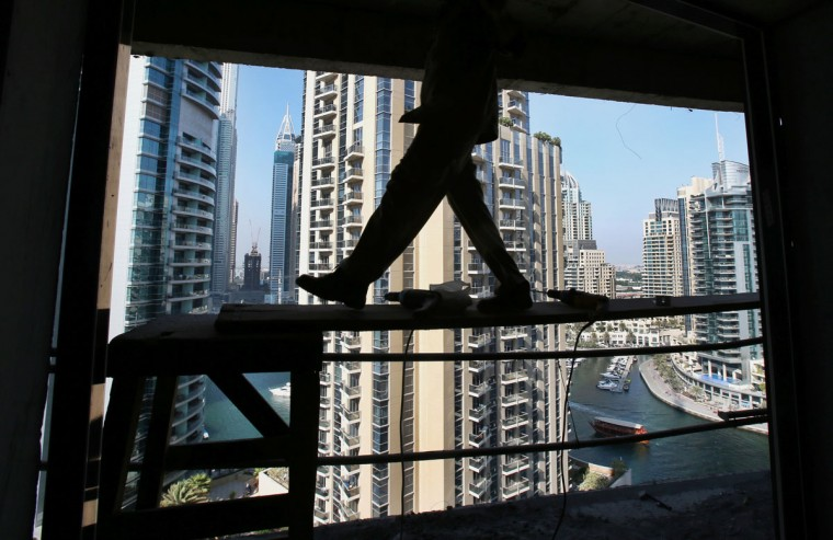 In this Aug. 10, 2015 photo, a worker walks on wooden scaffolding while fixing a window frame at a construction site in the Marina neighborhood of Dubai, United Arab Emirates. Armies of low-paid migrant workers, many of them from the Indian Subcontinent, leave behind families and travel to Dubai to build soaring towers like those in the Marina. While the wages they come for offer hope of a better life, they are far too meager for most to ever dream of calling the Marina they built home. (AP Photo/Kamran Jebreili)