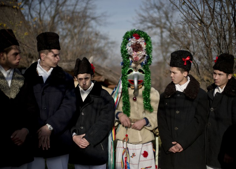 Men wearing traditional Romanian costumes, masks and animal furs prepare to perform in a show of winter traditions at the Village Museum in Bucharest, Romania, Sunday, Dec. 13, 2015. (AP Photo/Vadim Ghirda)