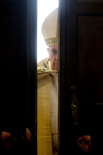 Pope Francis opens the Holy Door of St. Peter's Basilica at the Vatican, Tuesday, Dec. 8, 2015. Pope Francis pushed open the great bronze doors of St. Peter's Basilica on Tuesday to launch his Holy Year of Mercy, declaring that mercy trumps moralizing in his Catholic Church. (AP Photo/Andrew Medichini)