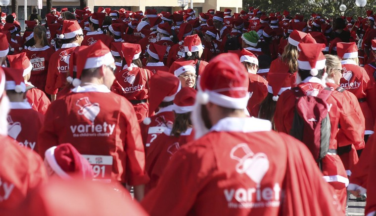 Thousands of people dressed as Santa Claus make their way on a 5-kilometer course during the annual Santa Fun Run in Sydney Sunday, Dec. 6, 2015. The Santa Fun Run was organized by Variety, an Australian charity that helps children who are sick, disadvantaged or have special needs. (AP Photo/Rob Griffith)